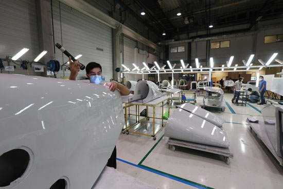 A worker inspects part of a Strata factory plane