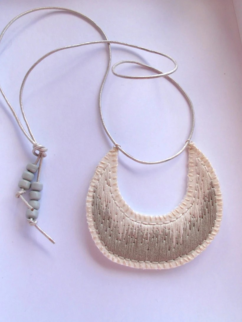 Crescent shaped pendant necklace embroidered with gray beads on silver leather cord