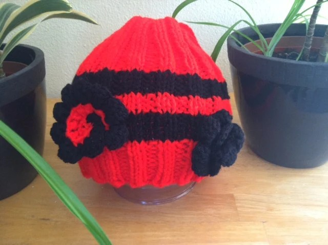Red and black knitted beanie hat with detachable flowers