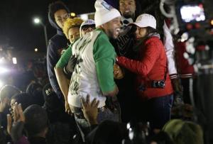 In this Nov. 24, 2014 file photo Louis Head, center front, Michael Brown's stepfather, and Brown's mother Lesley McSpadden, wearing sunglasses, react to the grand jury decision.