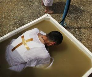 An Orthodox Christian pilgrim immerses himself in a tub of water taken from the Jordan River after it was blessed during a baptism ceremony at Qasr-el Yahud near Jericho April 14, 2009.