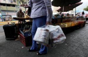 A woman who just bought toilet paper at a grocery store reads her receipt as she leaves the private store in Caracas, Venezuela, Wednesday, May 15, 2013.  First milk, butter, coffee and cornmeal ran short. Now Venezuela is running out of the most basic of necessities _ toilet paper. Economists...