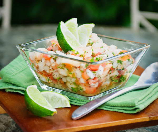 Shrimp ceviche with lime wedges