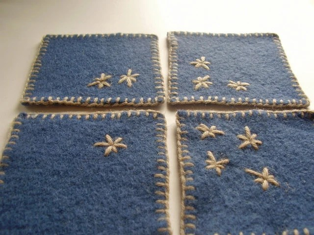 Set of 4 felted blue coasters, made from upcycled wool sweater, hand embroidered in beige with primitive stars design - rosemauve