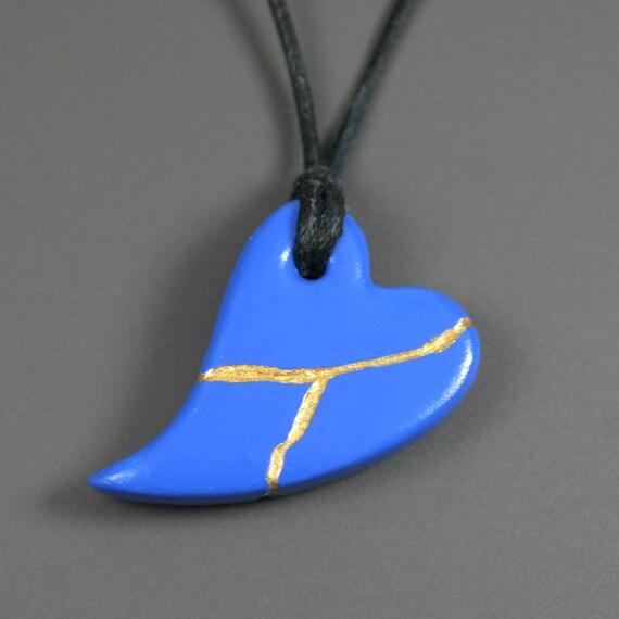 Blue faux kintsugi (kintsukuroi) broken heart pendant with gold repair in bisque porcelain on black cord