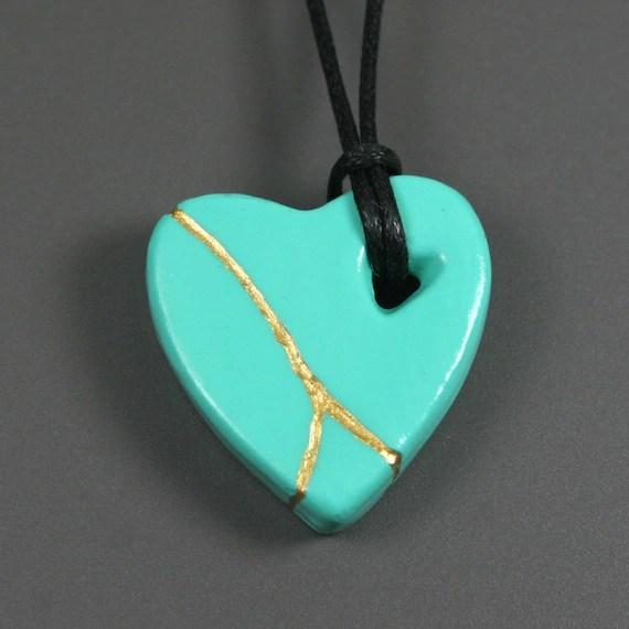 Sea green faux kintsugi (kintsukuroi) broken heart pendant with gold repair in bisque porcelain on black cotton cord