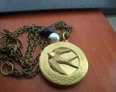 Peeta's locket  with  Mockingjay