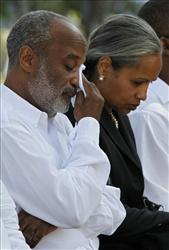 Haiti's President Rene Preval, left, wipes tears from his face during a national day of mourning as he sits with his wife Elisabeth Debrosse Preval in Port-au-Prince, Friday, Feb. 12, 2010.  Thousands of people gathered one month after the deadly magnitude-7 quake that left the Caribbean country struggling for survival.