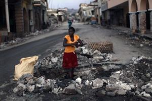 A woman, using water from a broken pipe, washes her hands in a street of Port-au-Prince, Thursday, Feb. 11, 2010. A powerful earthquake hit Haiti on Jan. 12.