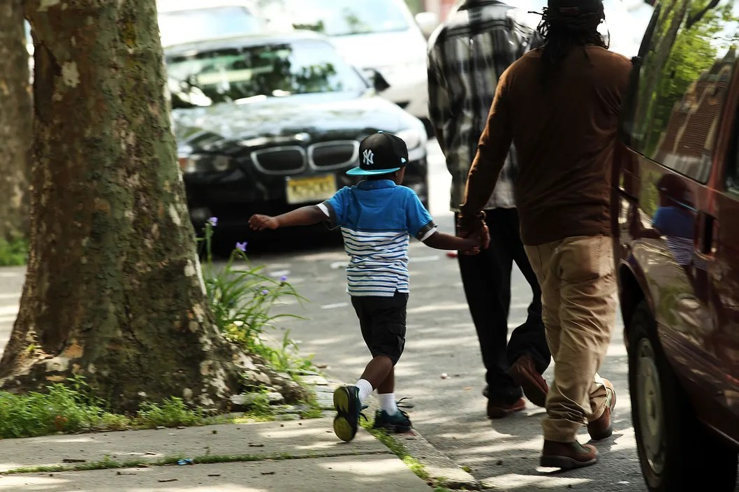 A man and child walk near the entrance to the building where two children were attacked with a knife last Sunday in an East New York apartment building elevator on June 4, 2014 in New York City. Prince Joshua Avitto (6) and Mikayala Capers, (7) were stabbed repeatedly by a man who later fled the scene and is still at large. Joshua died at Brookdale Hospital while Capers is in critical condition after undergoing surgery. It is believed that the suspect may have been involved with another recent stabbing in the same neighborhood.  (Photo by Spencer Platt/Getty Images)