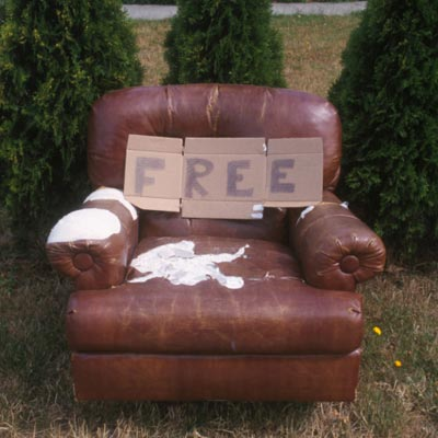 beaten up chair with free sign