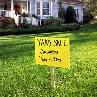 house with yard sale sign on lawn