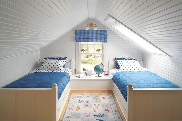 two kids bed with blue bedspreads set on opposite walls of a renovated attic room