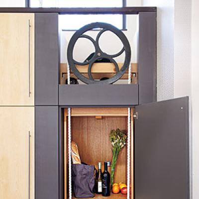 straight-on image of a dumbwaiter with an opening at the top that shows the large wheel mechanism, and an open door showing foodstuffs and wine reading to be moved to a lower floor