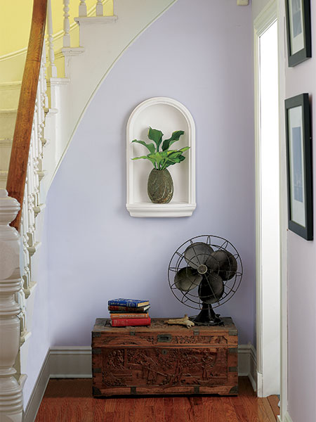 white wall niche set under a turning stair, with a green potted plant set on the niche shelf, set into a lavender wall