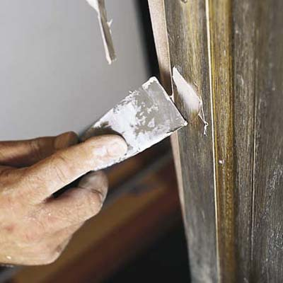 filling old screw holes with a filler applied with a putty knife