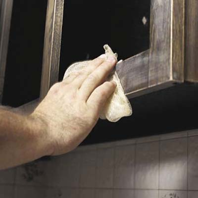 sanding the old finish on cabinet frames and wiping with a tack cloth