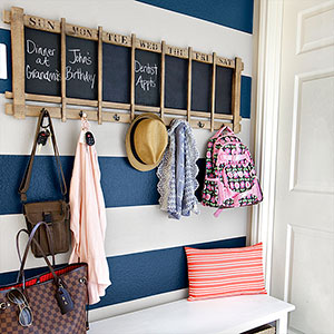 mudroom makeover after with focus on hooks, chalboard, storage bench