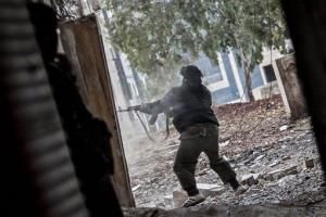 In this Dec. 11 photo, a Free Syrian Army fighter aims his weapon during heavy clashes with government forces in Aleppo, Syria.