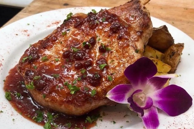 Grilled Frenched bone-in pork chop finished with a brandied lingonberry sauce
