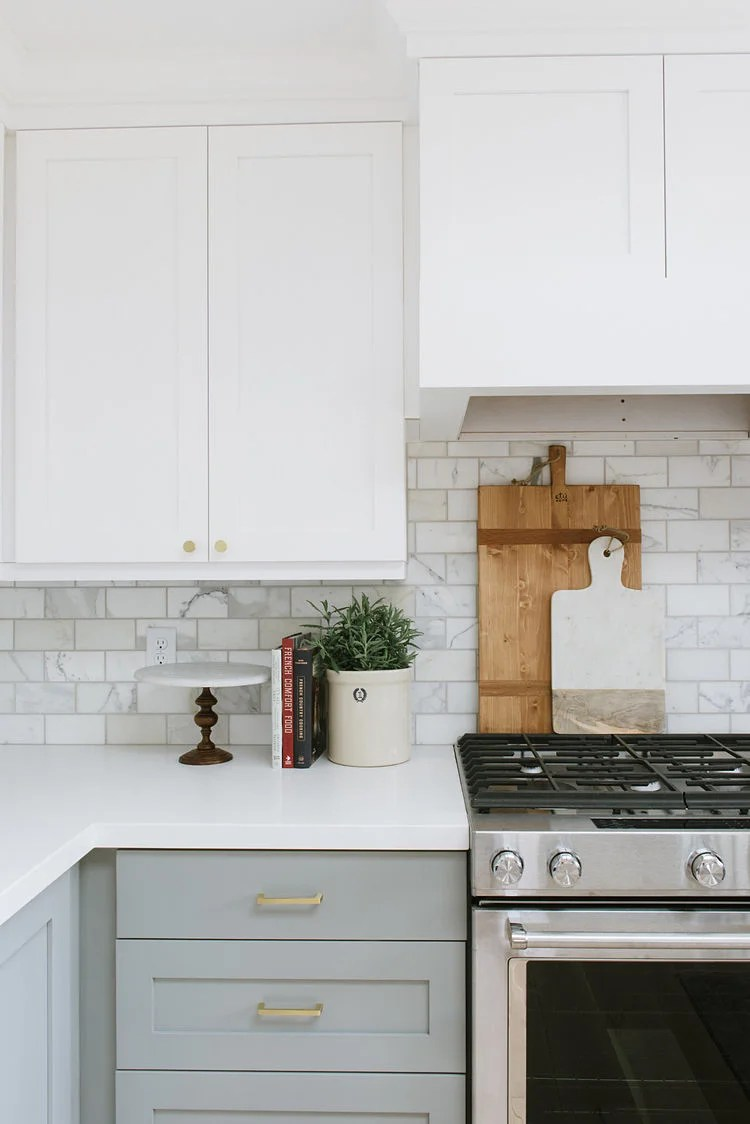 white upper cabinets and lower gray with subway tile backsplash
