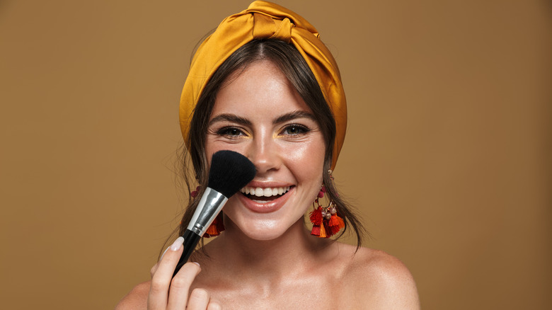 A woman applying blush with a brush