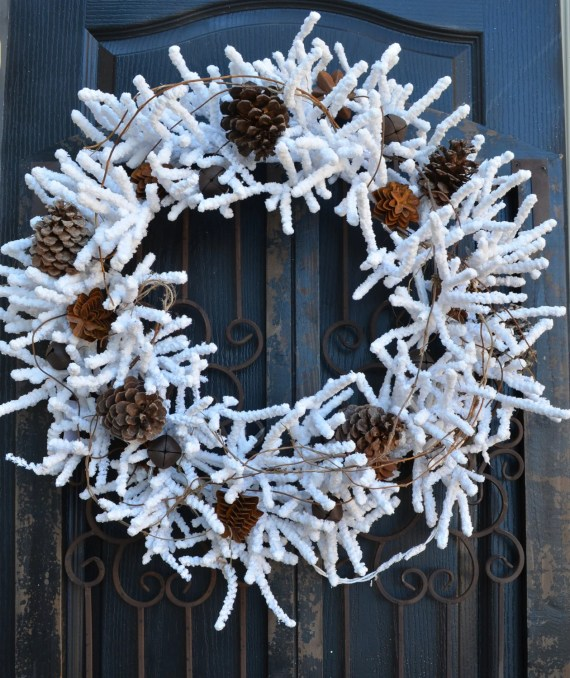 White flocked wreath lighted with rusted pinecones, natural pinecones and rusted jingle bells. - DoorBling