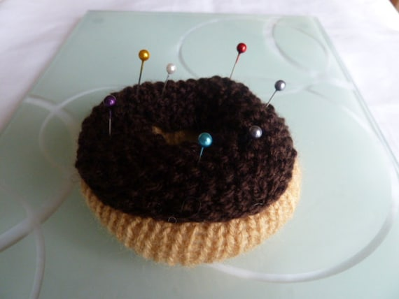 pin cushion donut  with choclate   icing and pins