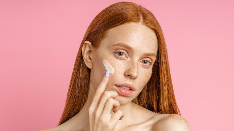 A woman applying cream on her face