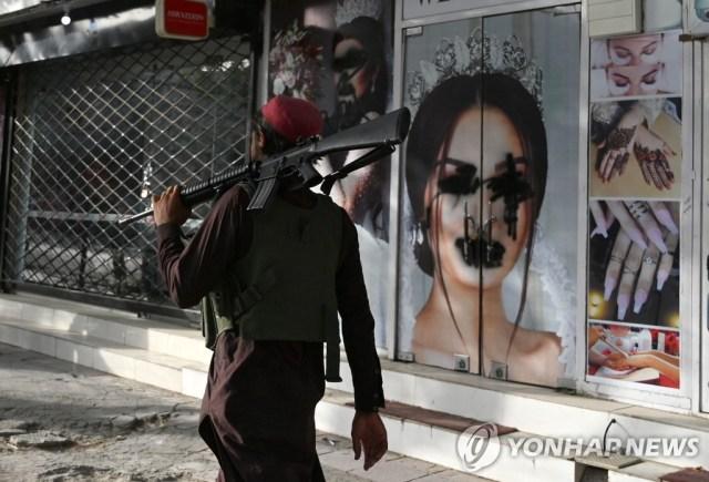 스프레이 뿌려진 카불의 미용실 광고사진 앞을 지나는 탈레반 대원