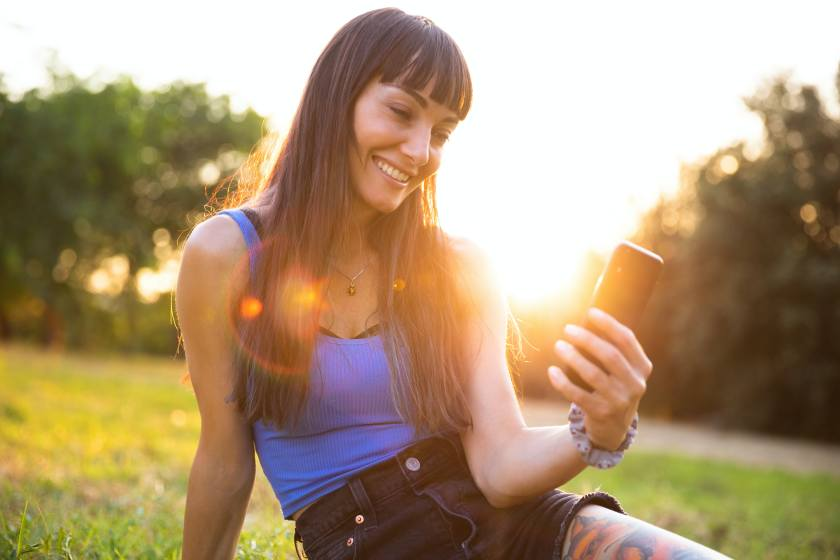 Young women using smartphone outdoors at sunset having the best week of August 30, 2021, by their zod...