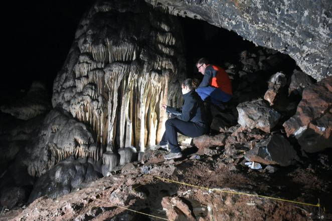 Researchers looking toward the massive speleothem of Cueva Ardales, with archaeological trench in th...