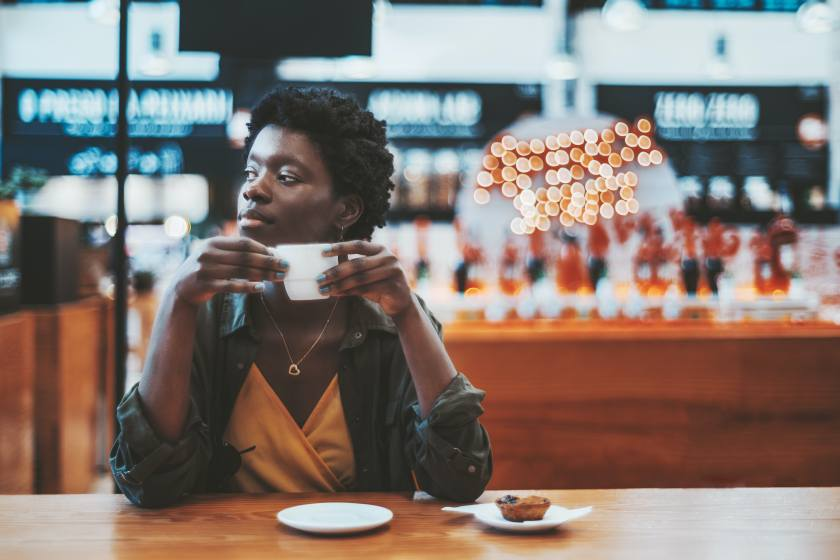 Pensive young African female is having breakfast in a cafe indoors of a mall or a food market and pensively looking aside while holding a cup of delicious coffee; a copy space place on the right