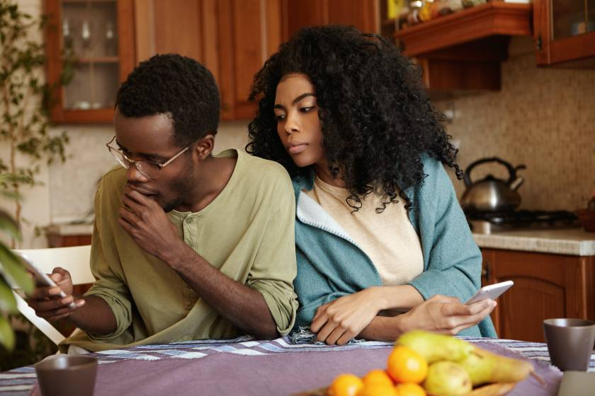 Relationships, secrecy, jealousy and infidelity concept. Suspicious jealous beautiful young dark-skinned female looking over her boyfriend's shoulder with curious expression, suspect of his betrayal