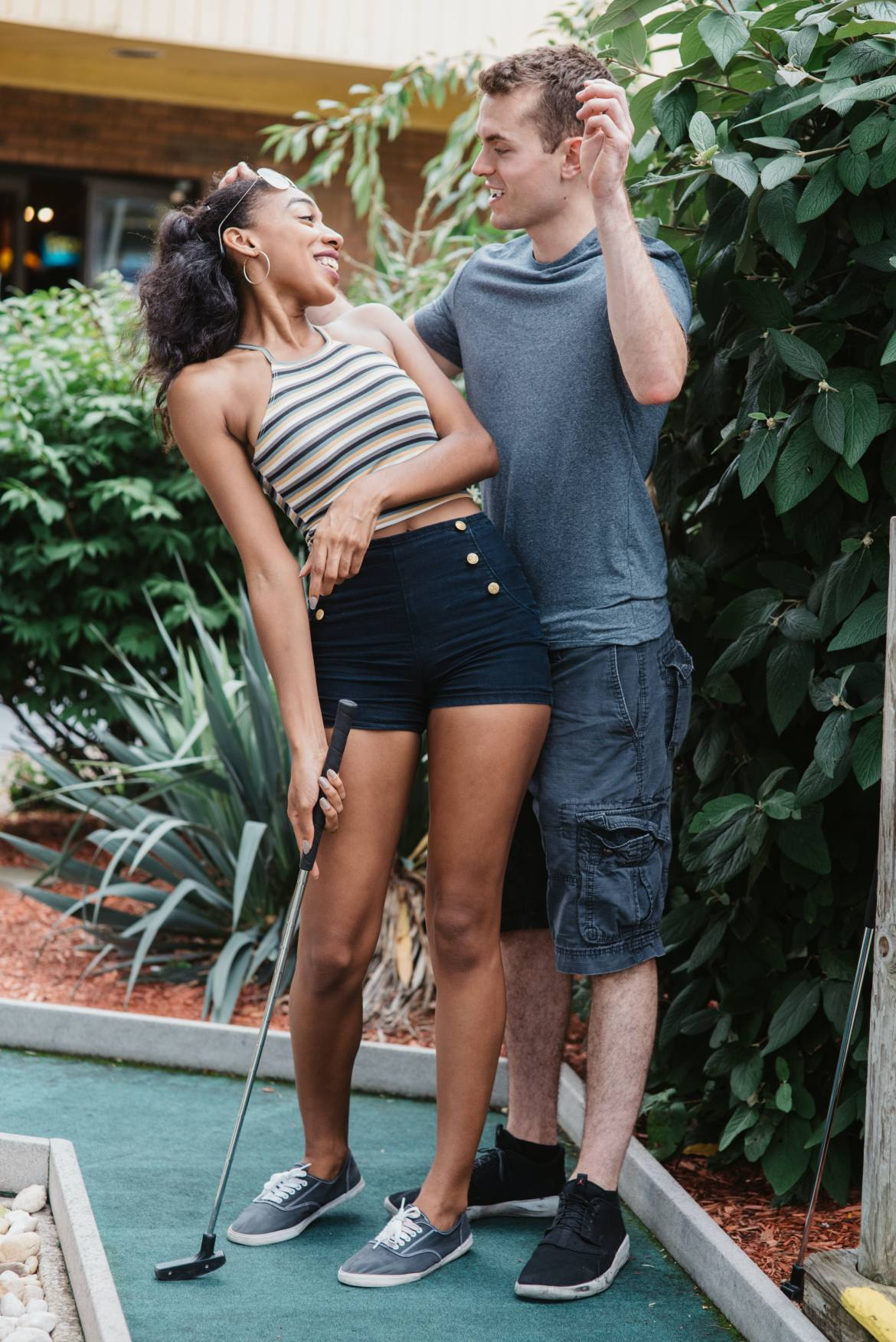 A young couple laughs while playing mini golf in the height of summer.