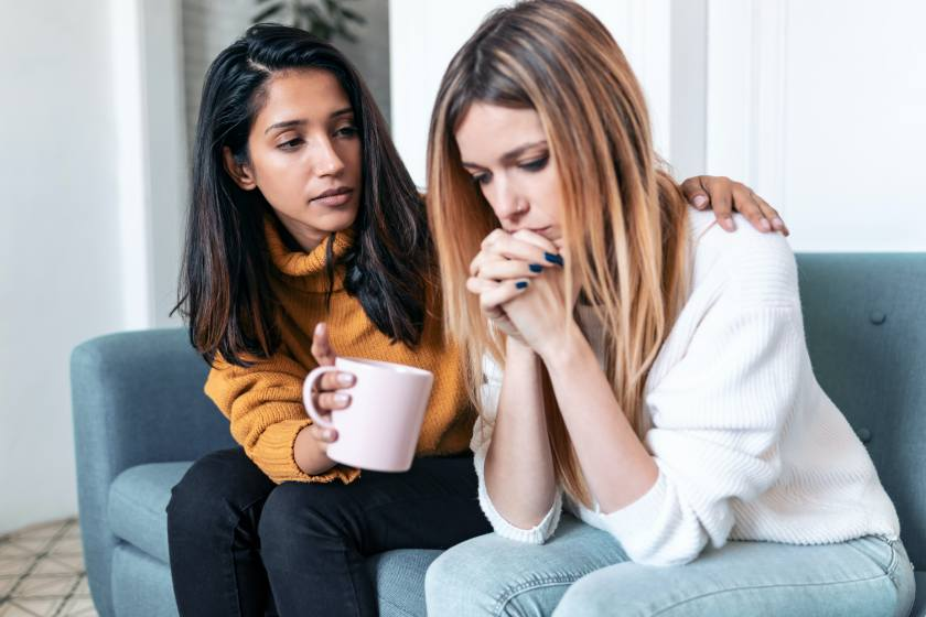 Shot of pretty young woman supporting and comforting her sad friend while sitting on the sofa at home.