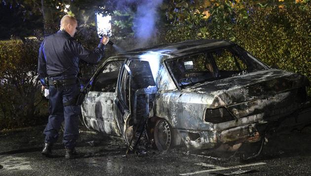 Ein Polizist vor einem ausgebranntem Auto (Bild: AP)