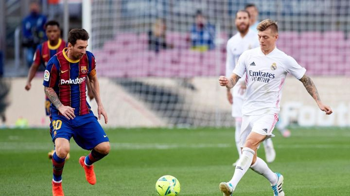 Lionel Messi of FC Barcelona competes for the ball with Toni Kroos of Real Madrid CF during the La Liga Santander match between FC Barcelona and Real Madrid at Camp Nou on October 24, 2020