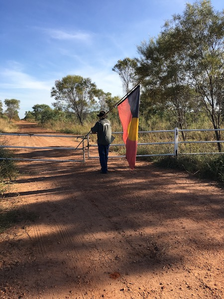 Micklo Corpus holds the Australian Indigenous flag at the gate of Buru Energy's Yulleroo site, situated on legally recognized ancestral lands of the Yawuru Aboriginal community. Image by Alexander Hayes via Flickr (CC BY 4.0).