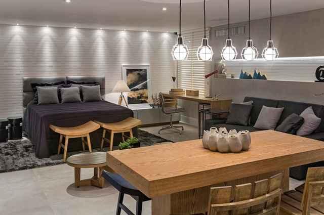 O ambiente integra quarto, escritório, sala de estar e cozinha, sendo que a delimitação de cada área é feita com o próprio mobiliário (Divulgação/Líder Interiores)