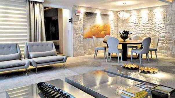 Na sala feita pelo arquiteto Robson Nascimento para um evento de decoração, o jogo de luz na parede de pedra torna o ambiente mais elegante