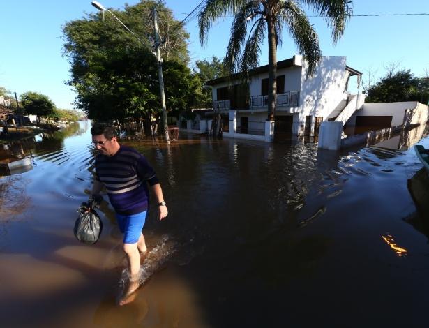 Homem caminha por rua alagada em Uruguiana, no Rio Grande do Sul