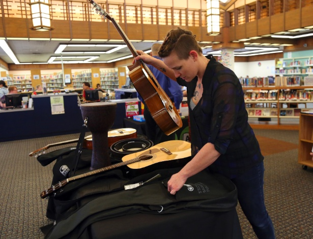 """Jessica Zacker, da equipe da Biblioteca Pública de Sacramento, arruma violões que fazem parte do projeto """"Biblioteca das Coisas"""" em Sacramento, na Califórnia, EUA"""