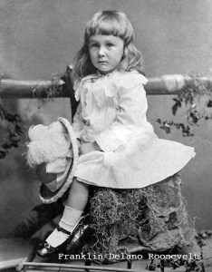 Franklin Delano Roosevelt 32 President as a child. In his white dress and frilly hat in hand. His hair is long and curly