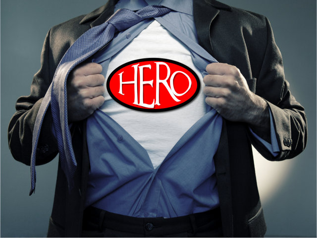 A man in suit and tie, his open shirt reveals a hero tee shirt | www.imjussayin.com