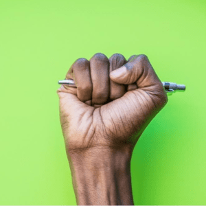 what's on talawa black first in black power salute with pen in hand against green back ground | www.imjussayin.com