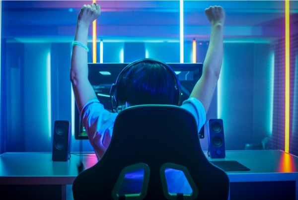 Teen playing a video game raises arms in victory