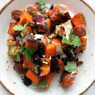 Roasted sweet potato salad with onions, cranberries and nuts, topped with goat cheese, or an everyday spin on a holiday dish