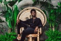 Adonis Bosso, clad in black, sits on a wicker chair surrounded by overgrown plants, placed before a concrete wall.