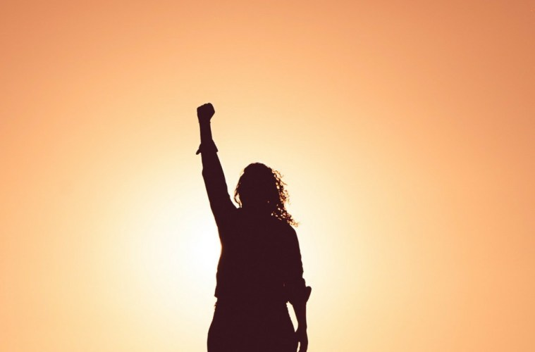 a person stood against an orange sunset with one hand as a fist in the air